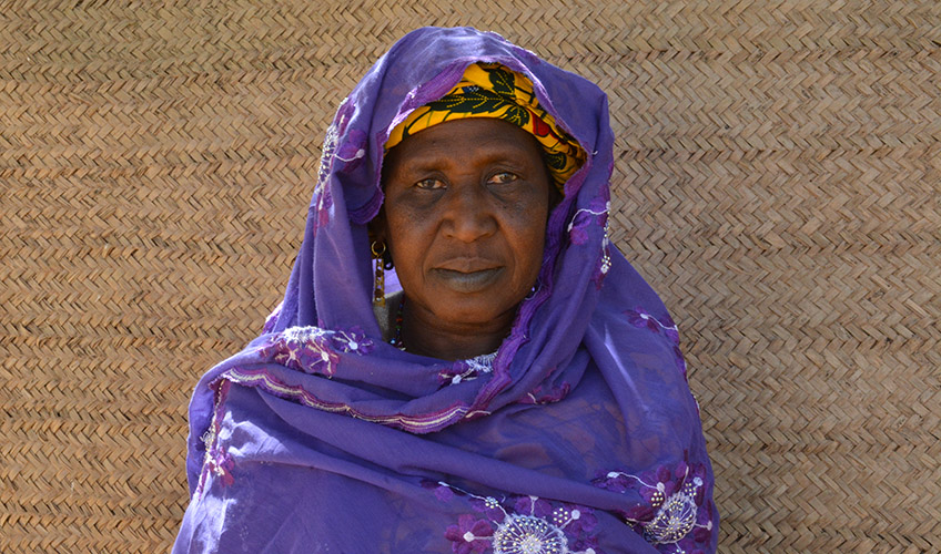 A close up of Aminatou wearing a purple shawl standing in front of a beige-coloured wall.