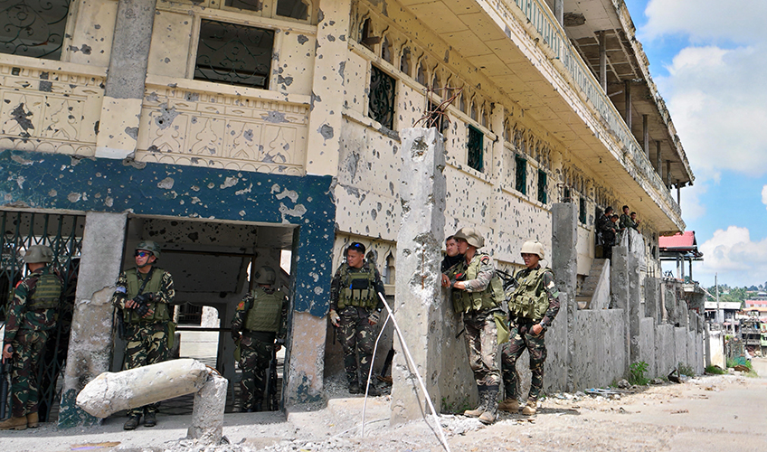 Soldiers stand around a war-damaged building in the Philippines.