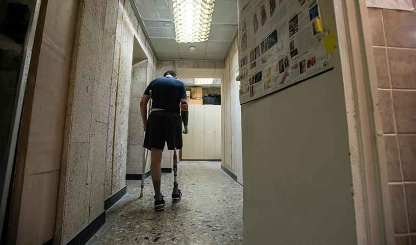 A Ukraine veteran walks down a corridor.
