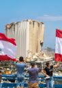 Lebanese wave the Lebanese flag at the scene of massive blast in Beirut