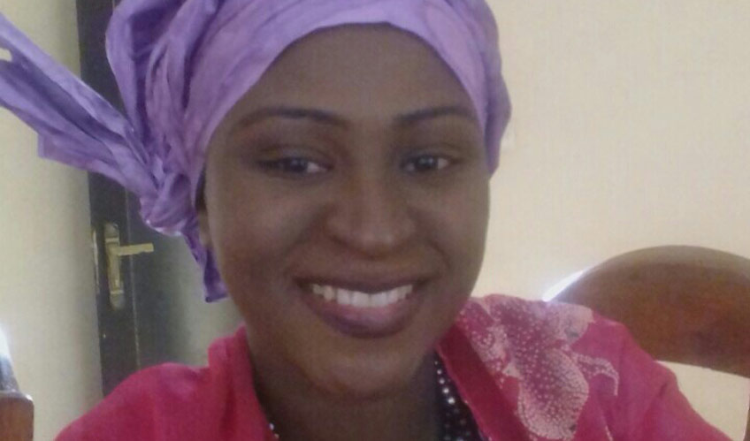 A close up of a woman smiles. She is wearing a purple headscarf and red top.