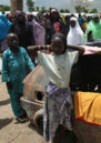 Young children and women gather around a disused car