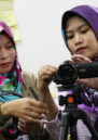 Two women examine the camera during filmmaking workshop