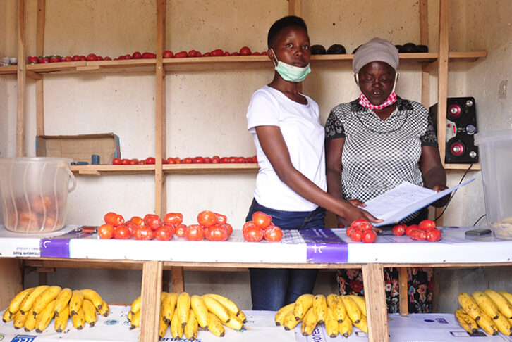 Julliene and her daughter stand to the right of their , Mauelle, at the market selling their goods at the market. They stand behind a market stall covered with tomatoes and bananas.