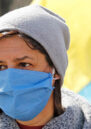A woman wearing a blue masks and grey woolly hat with a flag of Ukraine in the background.