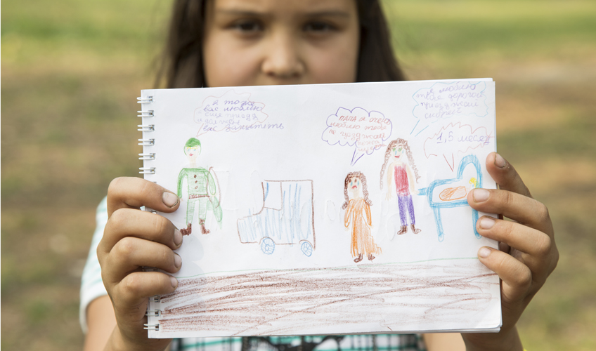Girl holds up a drawing of epople with speech bubbles and Russian text