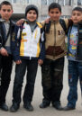 Four boys in Nagorny Karabakh pose in front of a large building.