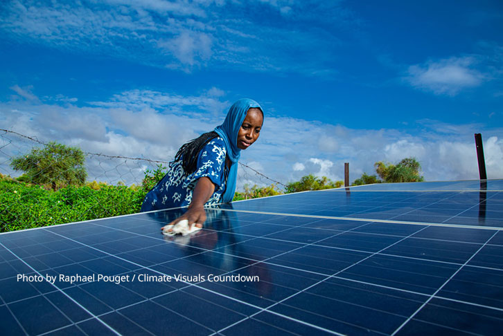 A woman cleans a solar energy panel - photo by Raphael Pouget / Climate Visuals Countdown